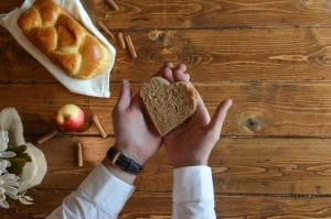 Photo: hand holding heart shaped piece of bread