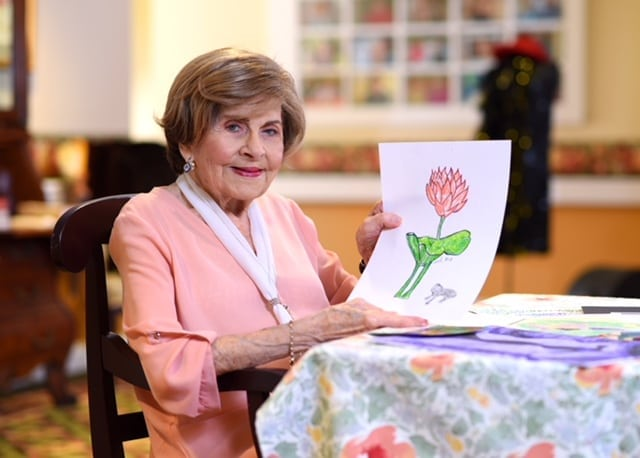 Photo: older woman holding up a drawing of a pink flower