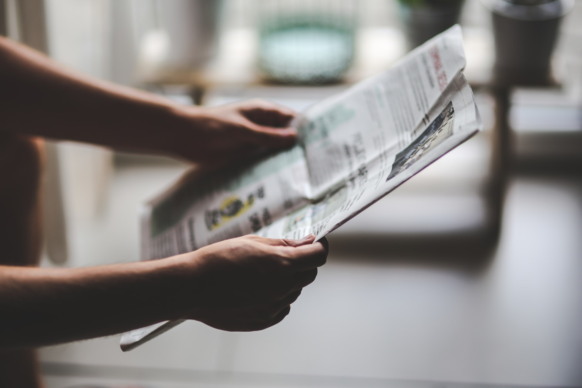 Photo: person holding a newspaper
